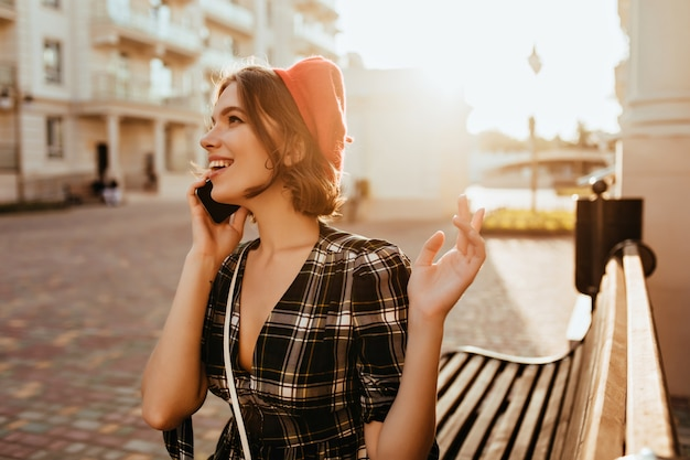 가을 날을 즐기는 우아한 옷에 긍정적 인 여성 모델. 전화 통화하는 빨간 베레모에 화려한 곱슬 여자의 야외 사진.
