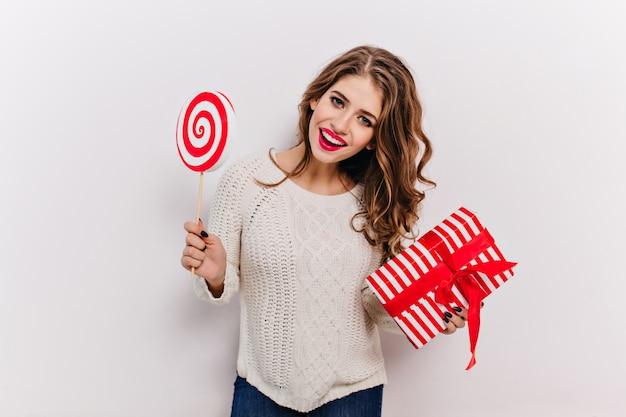 Modello femminile positivo in maglione lavorato a maglia e pantaloni blu con labbra rosse, in posa con il regalo di capodanno e la caramella nelle sue mani