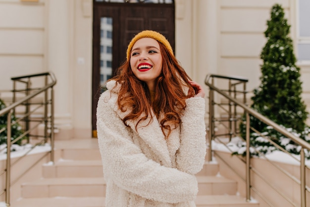 Positive female model laughing in winter day. blithesome ginger girl smiling with happiness.