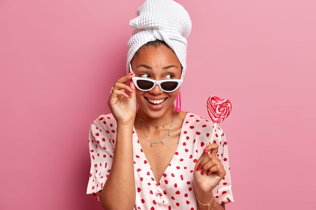 Positive female model wears sunglasses, dressed in casual clothes, holds appetizing heart shaped lollipop, gazes aside with glad expression,