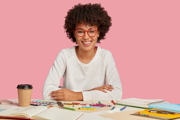 Positive female multiplier with afro haircut, pleasant smile on face, enjoys her work, has real talent for making illustrations, enjoys hot beverage, isolated over pink wall. creativity concept