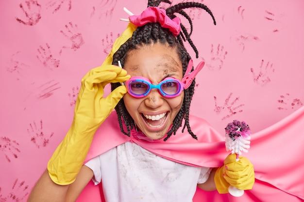 긍정적 인 여성은 슈퍼 히어로를 청소하는 척 고글에 손을 유지합니다 더러운 얼굴이 화장실 브러시를 착용하고 분홍색에 망토와 고무 장갑 포즈를 취합니다.