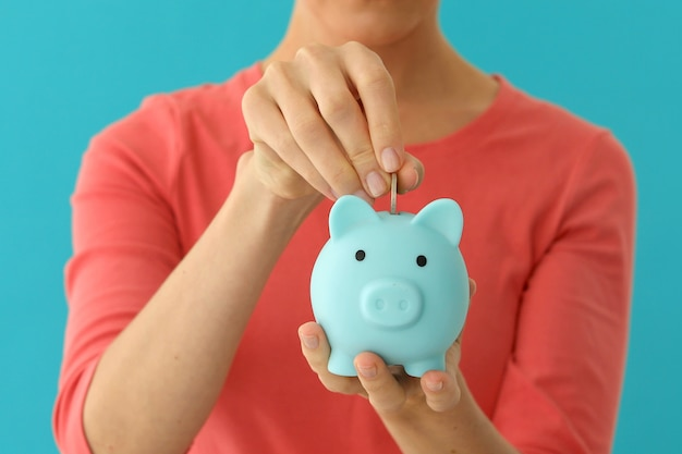 Positive female putting coin in piggybank, planning budget, financial savings