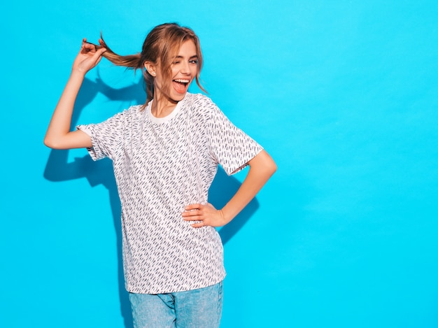Positive female smiling. funny model posing near blue wall in studio.winks