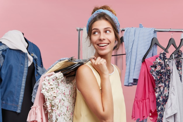 Positive female standing sideways holding with hangers of clothes on shoulders, looking aside waiting for her friend who is in fitting room. female model being glad to do shopping and buy new outfit
