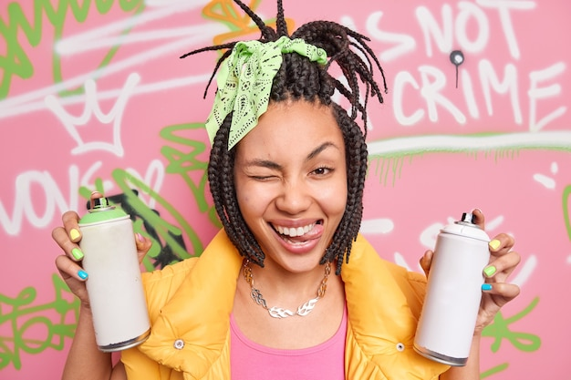Positive female street artist with trendy hairstyle winks eye sticks out tongue has fun while painting graffiti wall wears clolorful clothes holds aerosol bottles foolishes around