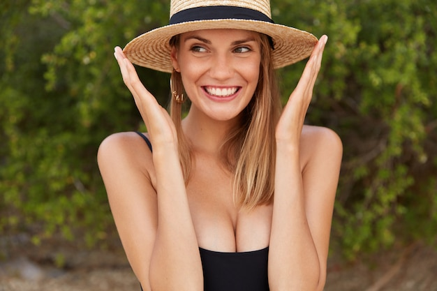 Positive female in summer hat looks happily away, wears black swimsuit, breathes fresh marine air. relaxed young woman enjoys summer holidays on coastline