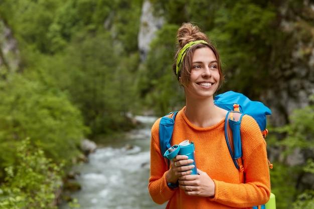 ポジティブな女性観光客が森の中の山の川の近くをさまよい、自然の構成に反対するポーズ