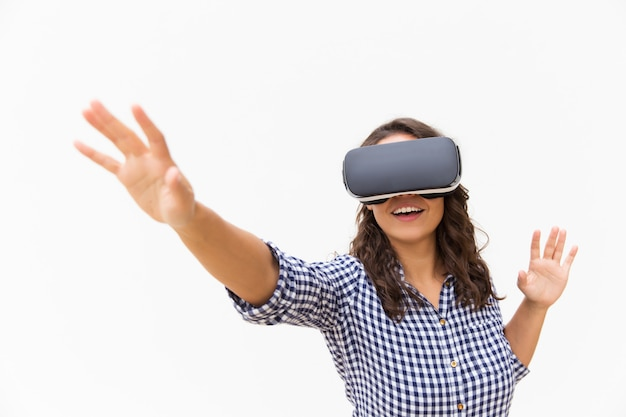 Positive female user in vr goggles touching air and smiling