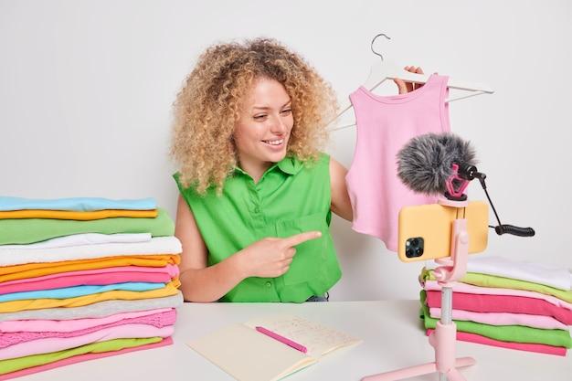 ポジティブな女性vloggerが広告フィルムを記録新しいビデオがスマートフォンのカメラの前で流行のファッショナブルな夏のシャツのポーズを宣伝
