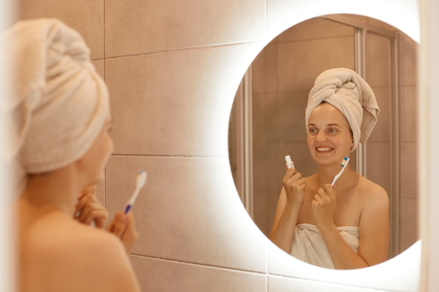 Positive female with white towel on her head holding toothpaste and toothbrush in hands, looking at her reflection in the mirror with happy facial expression.
