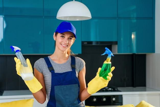 プロのクリーニングサービスの肯定的な女性労働者は、モダンな料理の背景にさまざまな洗浄剤を選択します。ハウスクリーニングサービスのコンセプト。