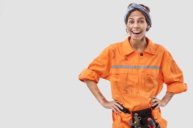 흰 벽에 포즈 긍정적 인 여성 노동자