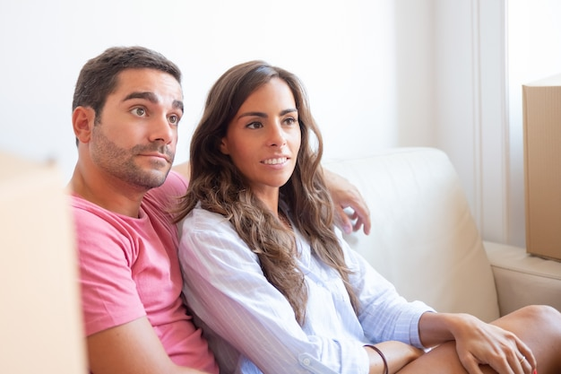 Positive focused latin couple sitting on couch among carton boxes in new apartment, looking away