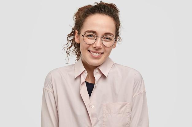 ポジティブそばかすのティーンエイジャーは歯を見せる輝く笑顔を持っており、丸い大きな眼鏡をかけています