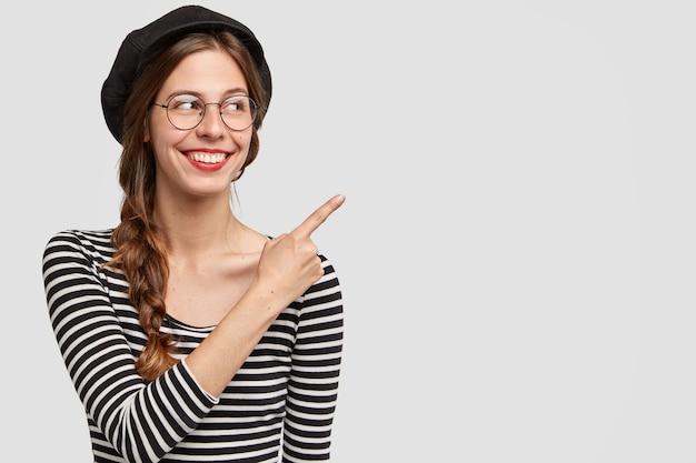 Позитивная француженка с привлекательным взглядом, счастливым выражением лица, показывает указательным пальцем в сторону, показывает пустое место, одетая в элегантную одежду