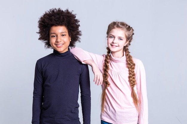 Positive friend. cheerful dark-haired boy with wild haircut standing near girl with blonde hair and blue eyes
