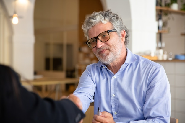 会議でパートナーと握手眼鏡で前向きなフレンドリーなビジネスマン