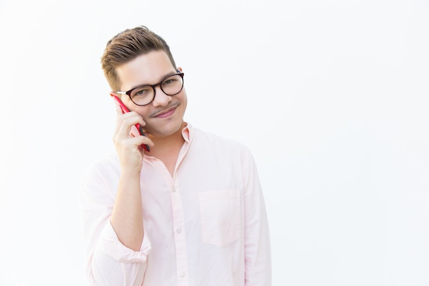 Positive friendly guy in eyewear talking on cellphone