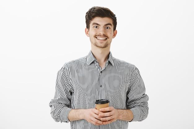 Позитивно-дружелюбный зрелый мужчина с усами и бородой в полосатой рубашке, держит чашку чая или кофе и радостно улыбается, встречает новых людей в офисе, небрежно и беззаботно разговаривает над серой стеной