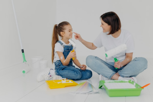 Positive friendly mother and daughter smeark each other with white paint