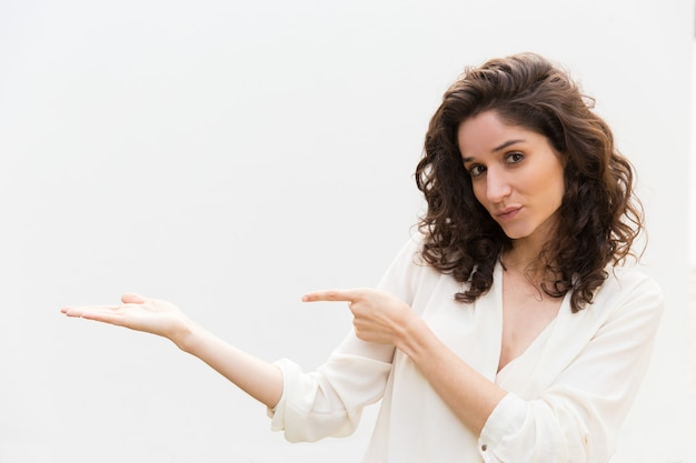 Positive friendly woman pointing finger and holding copy space