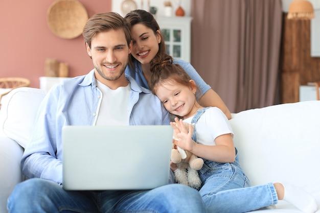 Позитивные дружелюбные молодые родители с улыбающейся маленькой дочкой сидят на диване вместе, отвечая на видеозвонок на ноутбуке и машут рукой в приветствии, отдыхая дома в выходные