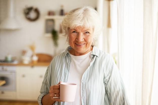 Donna anziana senior dall'aspetto amichevole positivo con capelli grigi e rughe che trascorre la giornata a casa, bevendo tè o caffè al mattino