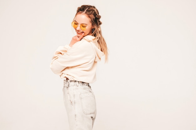 Positive and funny model posing on grey wall in studio in sunglasses