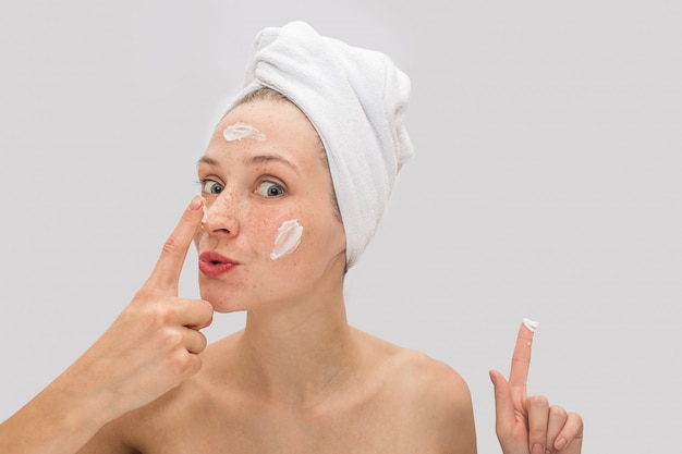 Positive and funny picture of young woman looks and touches her nose with finger. she has some face cream on her forehead and cheeks. also young woman points up.