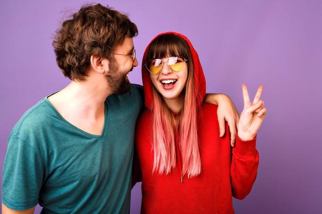 Positivo ritratto divertente di coppia felice che si diverte insieme, abbracci e risate, famiglia e amore, vestiti e accessori casual per giovani, che mostra gesto di pace, muro viola, relazione