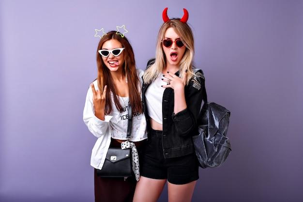 Позитивный смешной портрет симпатичных американок, наслаждающихся вечеринкой, молодежная хипстерская одежда, безумно беззаботное легкое настроение, две лучшие подруги.
