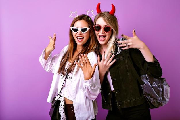 かなりアメリカ人の女性の肯定的な面白い肖像画は、彼らのパーティー、若者の流行に敏感な服、クレイジーなのんきな気分、2人の親友の女の子を楽しんでいます。