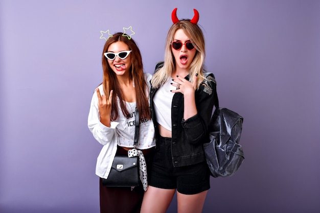Positive funny portrait of the pretty american women enjoy their party, youth hipster clothes, crazy carefree easy going mood, two best friends girls.
