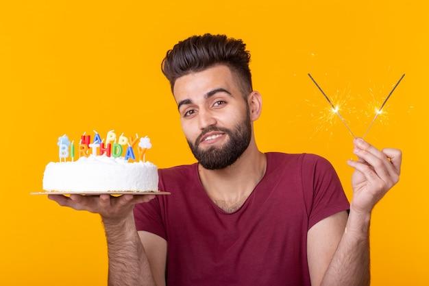 모자와 불타는 촛불, 노란색 배경에 포즈를 취한 손에 수제 케이크를 들고 긍정적인 재미 있는 젊은 남자. 기념일 및 생일 개념입니다.