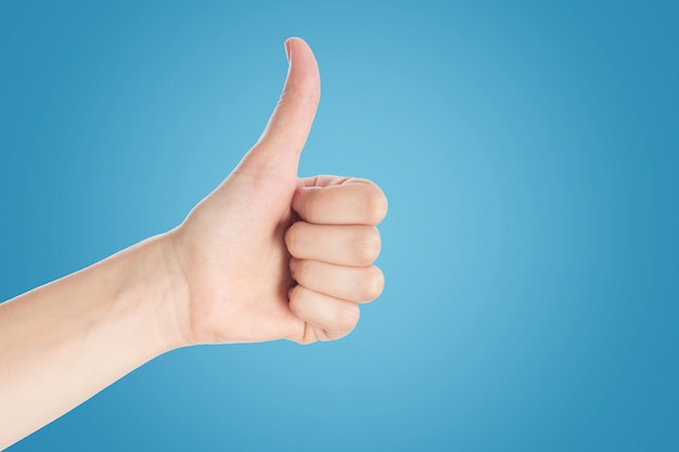 Positive gesture on a blue background. hand show thumbs up sign, close up