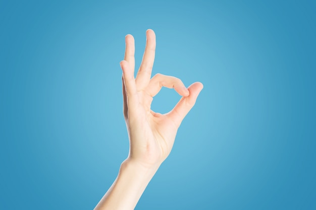 Positive gesture on a blue . hand show okay sign, close up