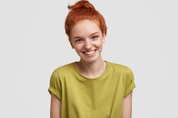 Positive ginger femae with freckled skin, broad smile, dressed in casual green t shirt, isolated over white wall