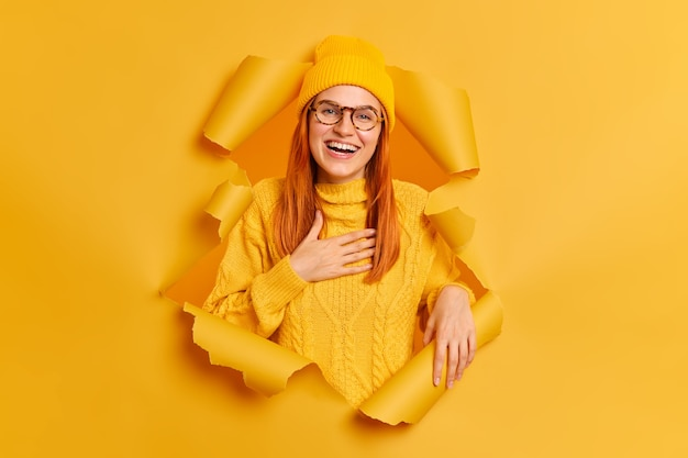 Positive ginger female model expresses sincere emotions keeps hand on chest feels gratitude smiles broadly wears yellow clothes breaks through paper ripped hole.