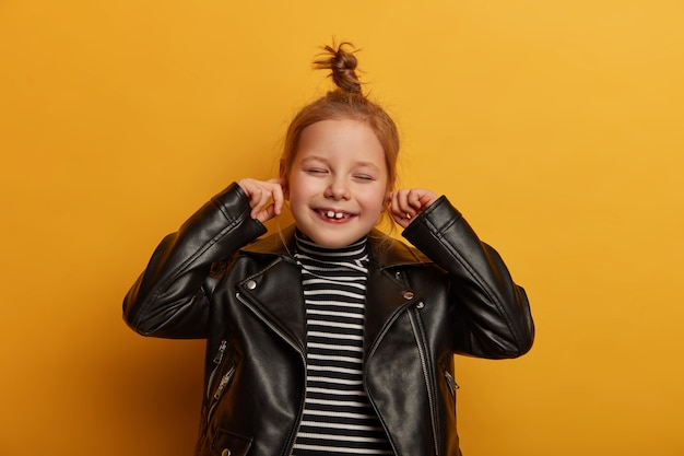 Positive ginger girl plugs ears, ignores loud sound and noise, closes eyes listens music stands satisfied indoor wears fashionable leather jacket, isolated on yellow wall, shows white milk teeth
