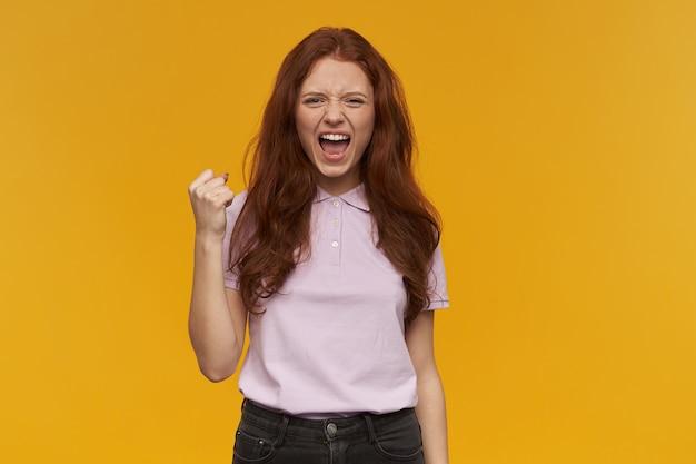 ポジティブな女の子、長い髪の魅力的な赤毛の女性。ピンクのtシャツを着ています。感情の概念。空中で拳を上げます。成功を祝う。オレンジ色の壁に隔離