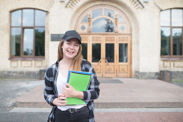 Positive girl in casual clothing standing with books and notebooks on campus, looking at the camera and smiling.
