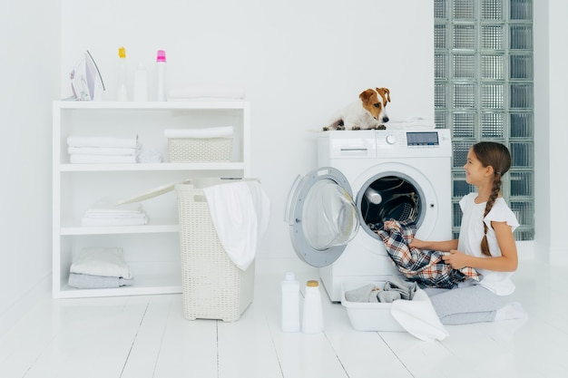 Positive girl emptying washing machine, holds clean checkered shirt, looks with smile at favourite pet who helps with doing laundry, poses on white floor with basin full of clothes, cleaning agents.