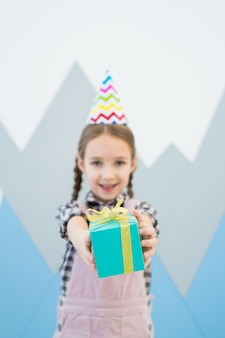 Positive girl giving gift box