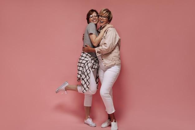 Ragazza positiva in maglietta grigia e camicia a quadri sorridente e abbracciando donna moderna con capelli biondi in pantaloni bianchi e giacca beige su sfondo rosa.