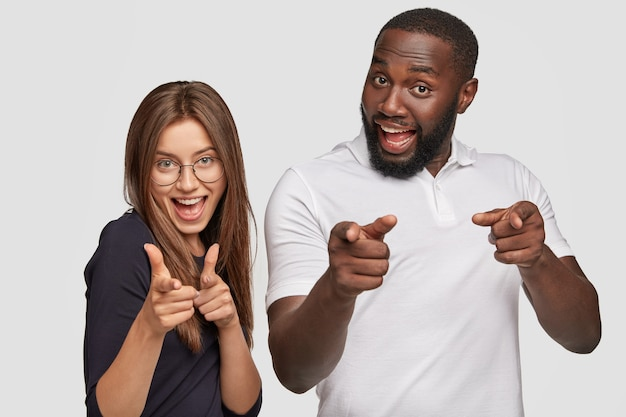 Positive girl and guy of different races make finger gun gesture, smile positively, express their choice