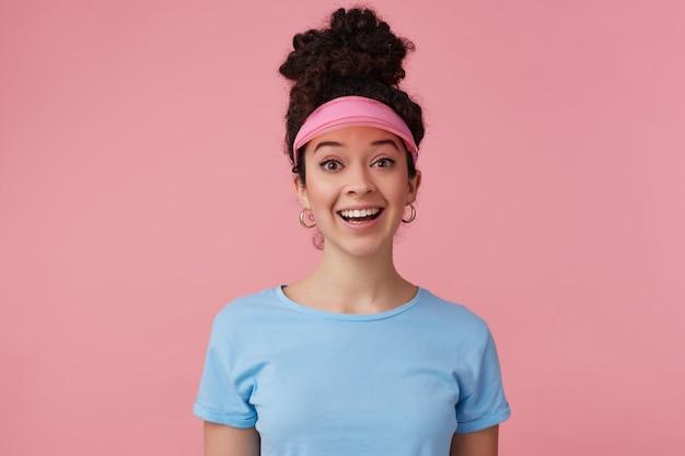 ポジティブな女の子、暗い巻き毛のお団子を持つ幸せそうな女性。ピンクのバイザー、イヤリング、青いtシャツを着ています。補っている。感情の概念