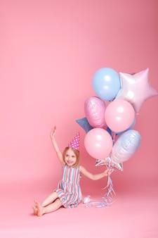 誕生日にピンクの表面の風船に満足しているポジティブな女の子