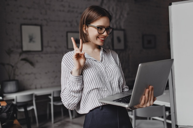 Positive girl in headphones and glasses shows peace sign, talking on video in laptop at workplace.