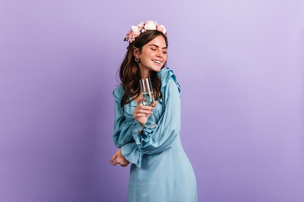Positive girl in high spirits laughs while enjoying party on purple wall. model in blue outfit holding glass of champagne.